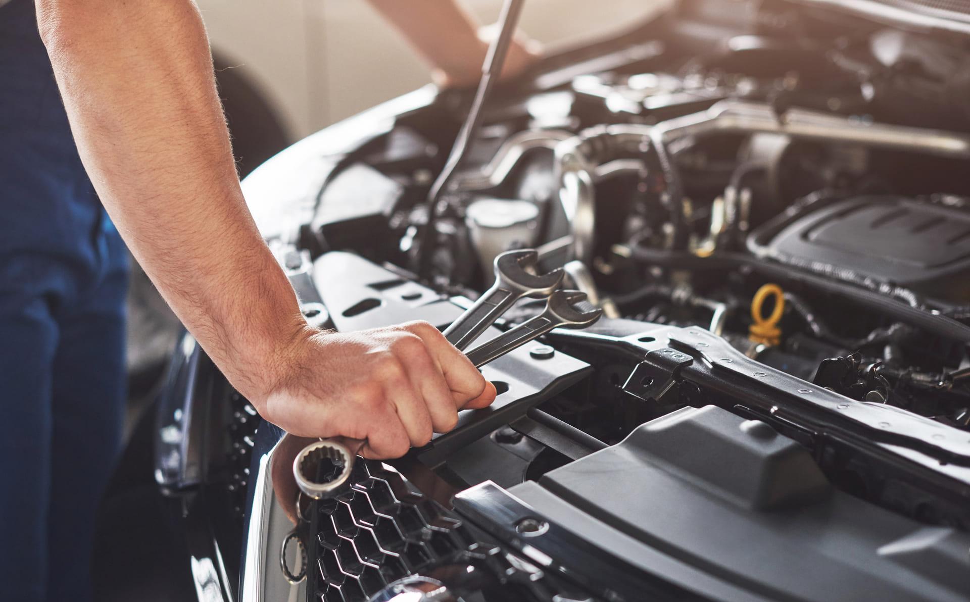 muscular car service worker repairing vehicle